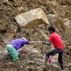 A man helps another make his way through deep mud at the site of a landslide at the Koslanda tea...