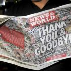 A man looks at a copy of the final edition of the News of the World newspaper in Waltham Cross,...