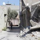A man walks past damaged buildings in Duma neighbourhood of Damascus, Syria. REUTERS/Bassam Khabieh