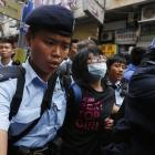 A masked protester is taken away by the police during a demonstration against mainland traders,...