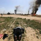 A member of militias known as Hashid Shaabi kneels as he celebrates victory while smoke rises...
