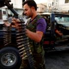 A member of the Free Syrian Army carries ammunition as he prepares for their patrol in Attarib,...