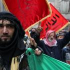 A member of the Free Syrian Army flashes the victory sign during a protest against Syria's...