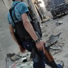 A member of the Free Syrian Army walks amongst damage in the old city of Homs. REUTERS/Shaam News...
