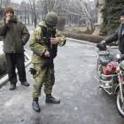 A member of the Ukrainian armed forces offers local residents a chance to join people who are...