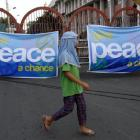 A Muslim girl walks past a banner backing a framework agreement between the Philippines...