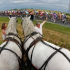 A pack of riders cycles past spectators with horses during the fifth stage of the 99th Tour de...