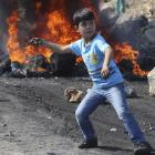 A Palestinian boy uses a sling to throw stones towards Israeli soldiers during clashes following...
