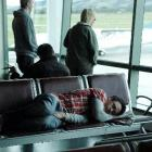 A passenger sleeps at Dunedin International Airport yesterday, with one of Air New Zealand's...