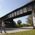 A pedestrian walks under the bridge where three teenagers were walking when they were hit and...