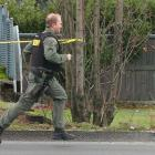 A Pierce County Sheriff deputy runs to the site where four police officers were killed in an...