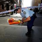 A police officer carries a bouquet under cordon tape as floral tributes are relocated after the...