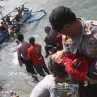 A police officer carries an unconscious child who was on a boat that capsized late off the coast...