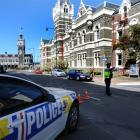 A police officer diverts traffic away from the Dunedin court house yesterday. Photos by Staff...
