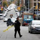 A police officer gathers police tape on Metcalfe Street following the shootings in downtown...