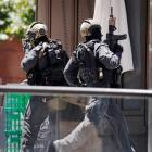 A police officer runs across Martin Place near Lindt cafe, where hostages are being held, in...