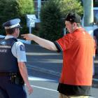 A police officer talks to Caltex Anthony Motors attendant Harrison Skeggs after he helped...