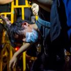 A pro-democracy protester is detained by police during a confrontation at Mong Kok shopping...