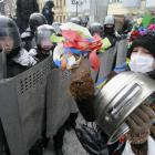 A pro-European protester stands in front of riot police.  Photo by Reuters.
