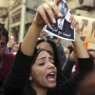 A protester chants anti-government slogans while holding a poster of Egyptian Interior Minister...