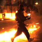 A protester runs with a petrol bomb towards riot police guarding the parliament in Athens'...