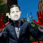 A protester wearing a mask of Syrian President Bashar al-Assad holds up hands covered in red...