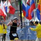 A runner and race officials react to an explosion during the Boston Marathon in Boston,...