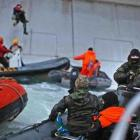 A Russian Coast guard officer is seen pointing a gun at a Greenpeace International activist as...