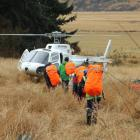 A search and rescue team moves to a helicopter in a paddock at Birchwood to be airlifted out in...
