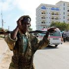 A Somali government soldier carries his gun as he patrols outside the Jazeera Palace hotel in...