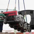 A steam engine is lifted on to a truck by mobile crane in Dunedin before being trucked north for...
