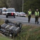 A Surete du Quebec (SQ) officer investigates an overturned vehicle in Saint-Jean-sur-Richelieu....