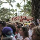 """A surfboard with the message """"Stop the attacks"""" is seen during a demonstration attended by 300..."""