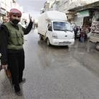 A Syrian rebel controls traffic in Idlib, Syria. Activists say Syrian troops have continued...