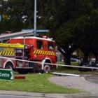 A truck and trailer unit lies on its side by the Dunedin Botanic Garden in Great King St after it...