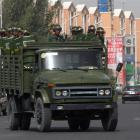 A truck carrying security personnel with anti-riot gear makes its ways through the street in Kuqa...