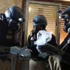A UN chemical weapons expert holds a plastic bag containing samples from the site of an alleged...