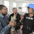 A United Nations observer is shown a shell last week after a bombardment of Homs city. Photo by...