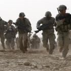 A US soldier returns fire as others run for cover during a firefight with insurgents in the...