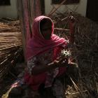 A villager sits on the debris of a damaged house as she holds a metal propeller of a mortar that...