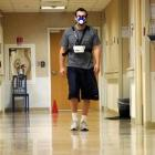 A volunteer walks a hallway wearing instruments that measure oxygen consumption as part of a 50...