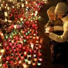 A woman and child light a candle to pay respects to fallen anti-Yanukovich protesters in the...