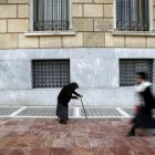 A woman beggar walks by the Bank of Greece in central Athens. REUTERS/Yannis Behrakis