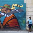 A woman stands on the street in downtown Havana.  From bus drivers to bartenders and ballet...