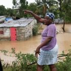 A woman surveys the damage of flooding to her home by the rising Riviere Grise after the brunt of...