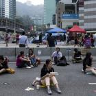 A woman takes her lunch while sitting on a highway, part of an area blocked off by protesters of...