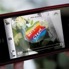 A woman uses her iPhone to take a photo of a sticker on a flower offered in memory of Apple co...
