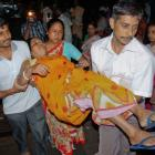 A woman who was injured by a stampede after an earthquake is carried to a hospital in the eastern...