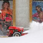 A worker clears snow off the sidewalk in front of a Victoria's Secret store in Boston,...