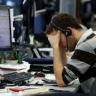 A worker on IG Index's trading floor in London holds his head in his hands as markets tumble...